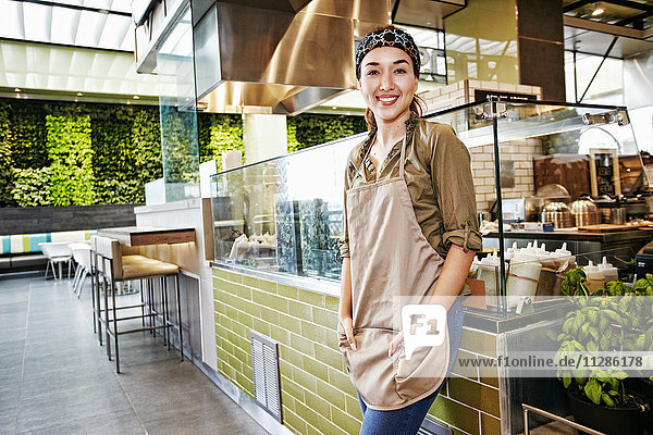 Portrait of smiling Mixed Race worker in food court