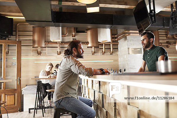 Man in coffee shop talking to bartender