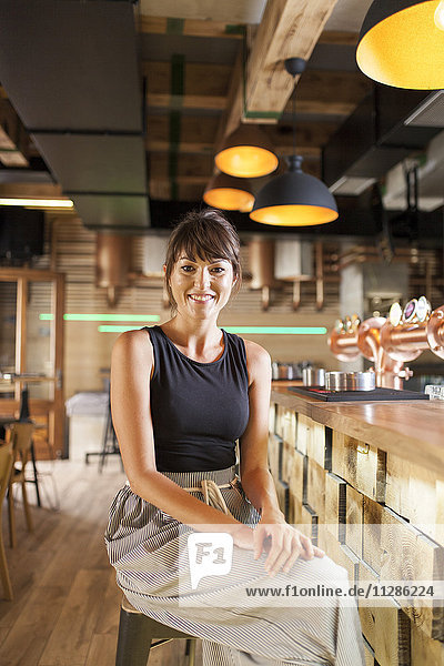 Woman with brown hair sitting at bar counter in coffee shop
