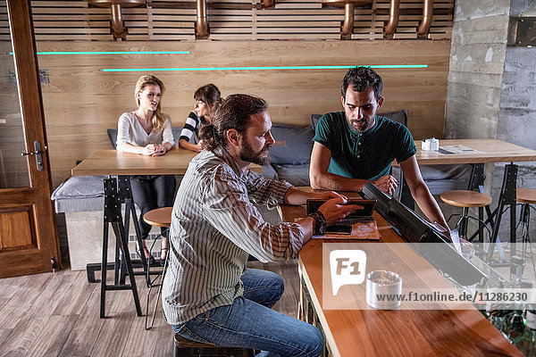 Male guest and bartender talking at bar counter in coffee shop
