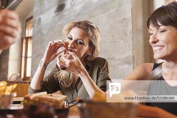 Two women in coffee shop eating snacks