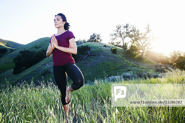 Mixed Race woman practicing yoga on hill Mixed Race woman practicing yoga on hill