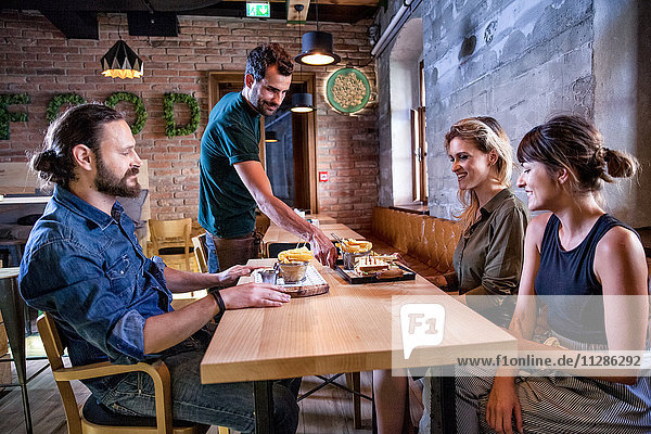 Waiter serving dishes to friends in restaurant