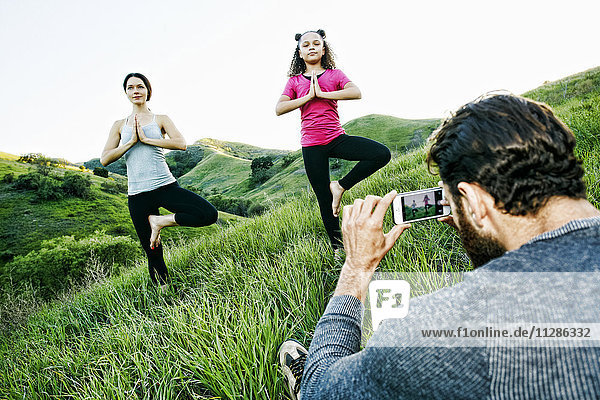 Man photographing wife and daughter practicing yoga on hill Man photographing wife and daughter practicing yoga on hill