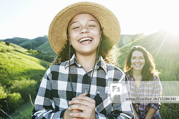 Portrait of mother and daughter laughing on hill