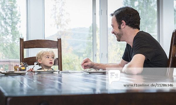 Caucasian father and son eating food at table Caucasian father and son eating food at table