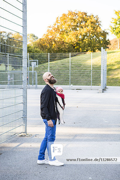 Father with baby girl in baby carrier on playing field