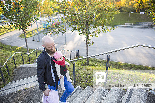 Father with baby girl in baby carrier walking up steps