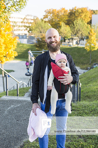 Portrait of father with baby girl in baby carrier