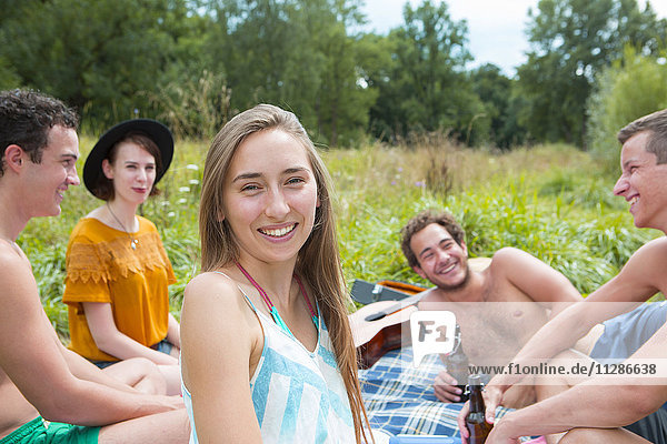 Group of friends relaxing on riverbank