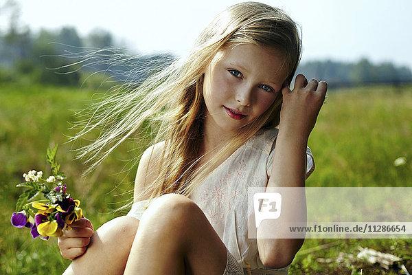 Caucasian girl holding flowers in windy field