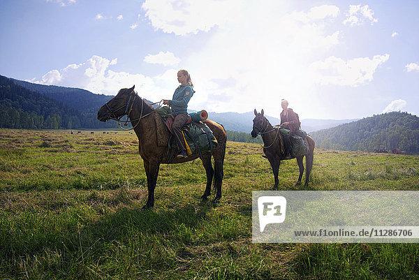Caucasian girls riding horses in field