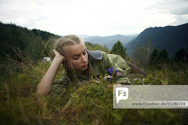 Caucasian girl holding wildflowers laying in grass on hill