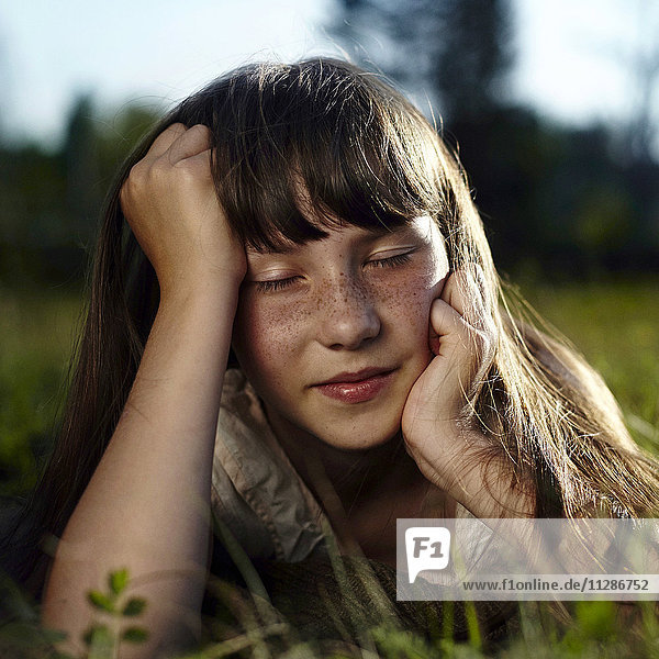 Caucasian girl with freckles laying in grass