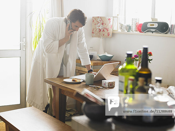 Man using Cell Phone and Laptop Computer in Kitchen