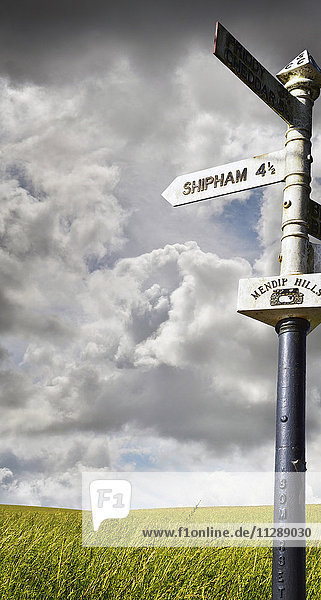 Old signpost with stormy sky and grassy field in the countryside in Sommerset  England