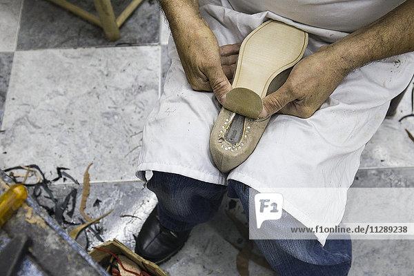 Schuhmacher beim Aufsetzen der Sohle auf einen Schuh in seiner Werkstatt Schuhmacher beim Aufsetzen der Sohle auf einen Schuh in seiner Werkstatt