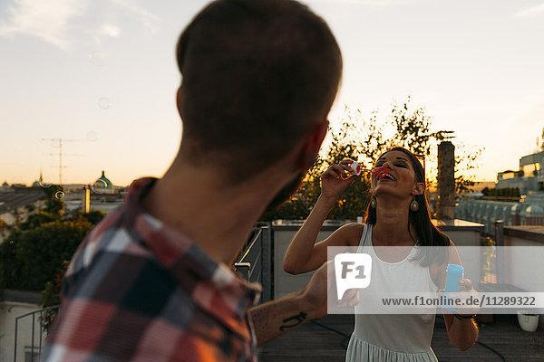 Junge Frau bläst Seifenblasen auf der Dachterrasse  während ihr Freund sie beobachtet. Junge Frau bläst Seifenblasen auf der Dachterrasse, während ihr Freund sie beobachtet.