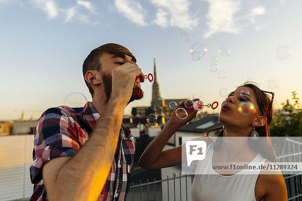 Österreich  Wien  junges Paar bläst Seifenblasen auf der Dachterrasse