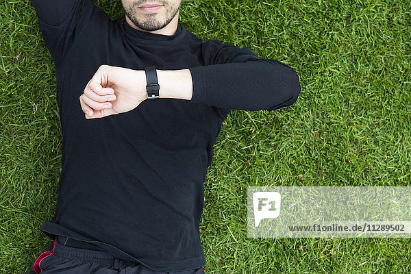 Jogger im Gras liegend mit Blick auf die Uhr