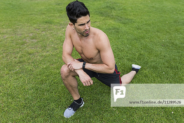 Barechested Athlet Stretching im Gras