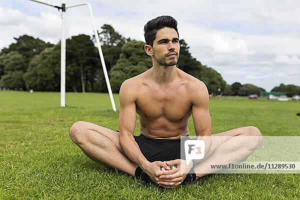 Nackter Athlet im Gras sitzend