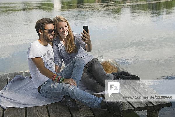 Lächelndes junges Paar sitzt auf einem Steg am See und nimmt einen Selfie.