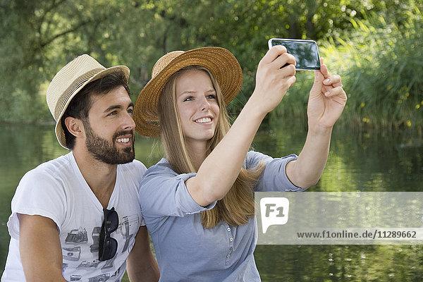 Lächelndes junges Paar an einem See mit einem Selfie