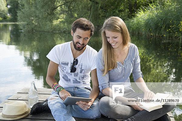 Lächelndes junges Paar am Steg am See mit Buch und Tafel