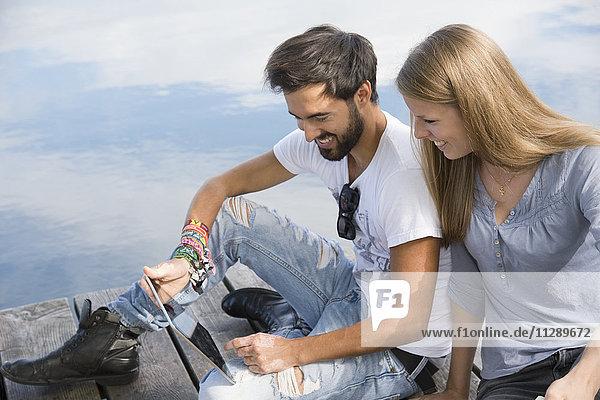 Lächelndes junges Paar sitzt auf einem Steg am See mit Tablette