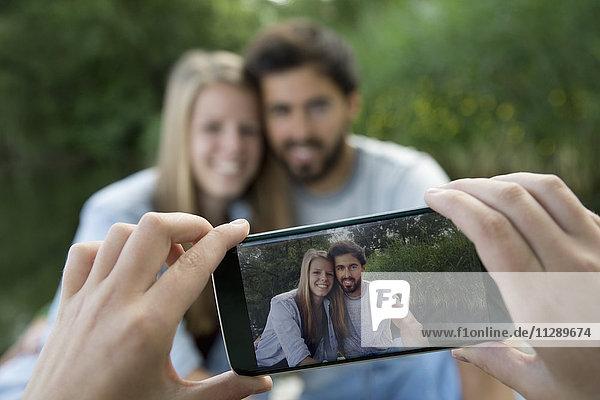Handybild eines lächelnden jungen Paares am See