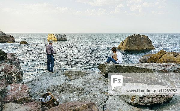 Älterer Mann beim Fischen am Meer mit Frau auf Felsen sitzend