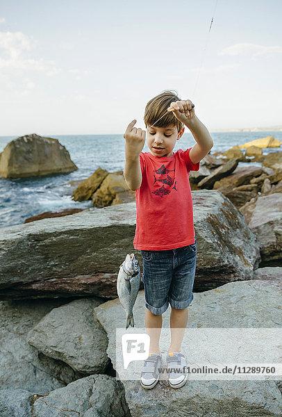 Junge mit Fisch an der Angelschnur
