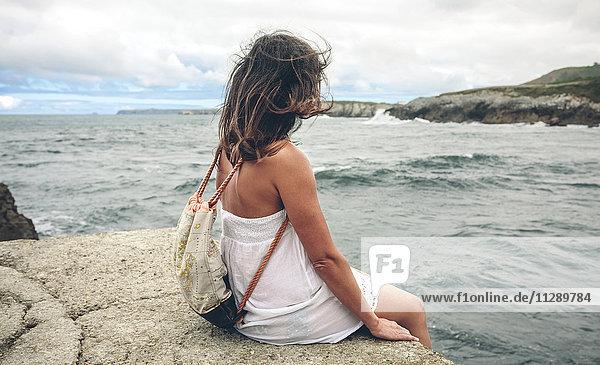 Frau mit Rucksack am Pier mit Blick aufs Meer