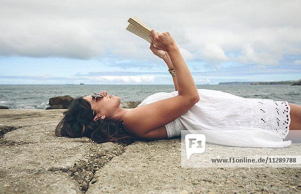 Frau liegt auf dem Pier und liest ein Buch.