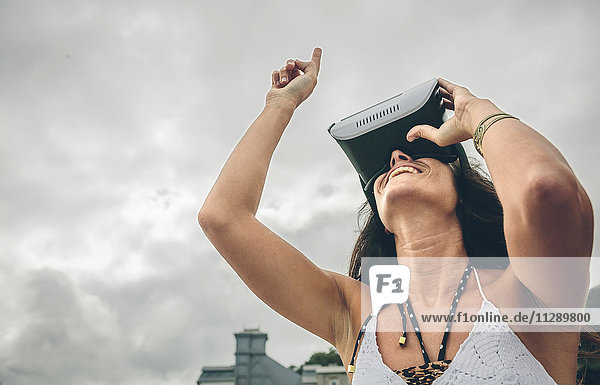 Smiling woman using Virtual Reality Glasses outdoors