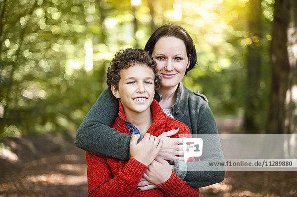 Porträt von lächelnder Mutter und Sohn im Herbstwald