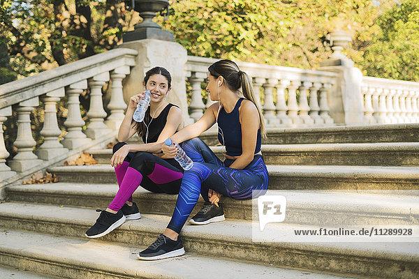 Zwei sportliche junge Frauen sitzen auf einer Treppe mit Flaschen und Ohrstöpseln.