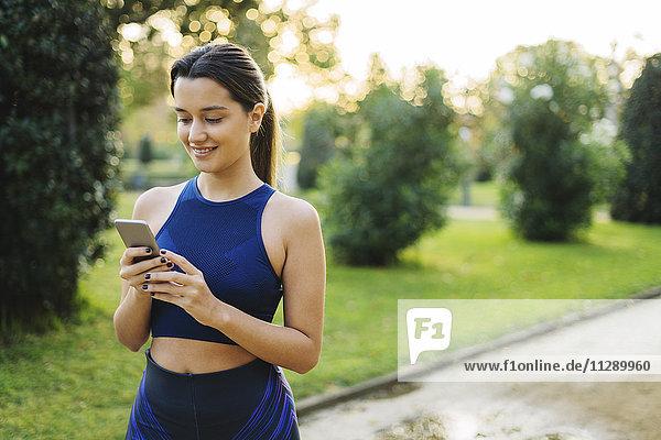Sportliche junge Frau beim Blick auf das Handy im Park