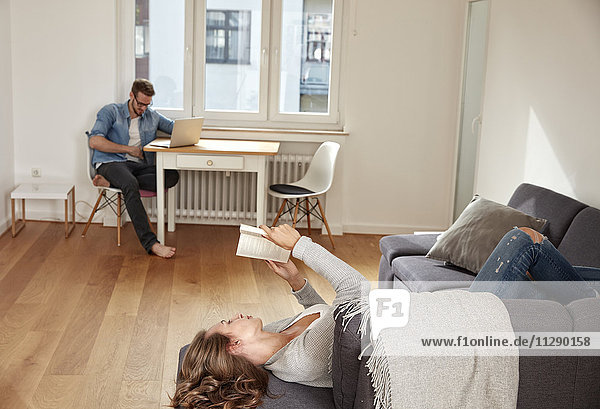 Paar Entspannung mit Buch und Laptop zu Hause
