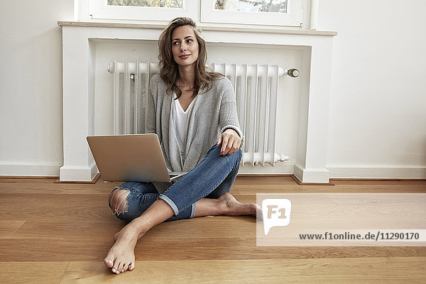 Smiling woman sitting on the floor with laptop