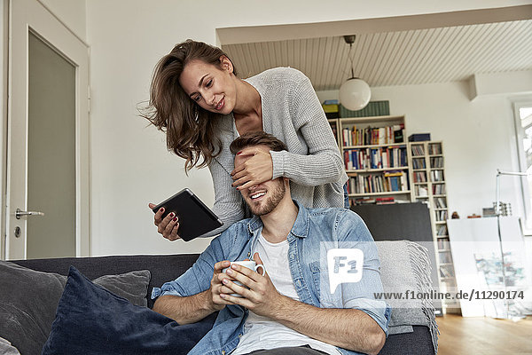 Frau überrascht ihren Freund  der auf der Couch im Wohnzimmer sitzt.