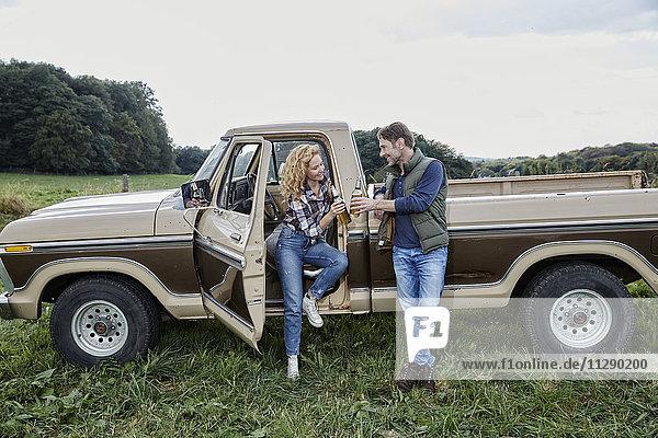 Paar am Pick-Up mit Bierflaschen