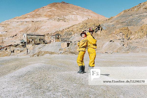 Bolivien  Potosi  zwei Touristen in Schutzkleidung stehen Rücken an Rücken vor dem Cerro Rico