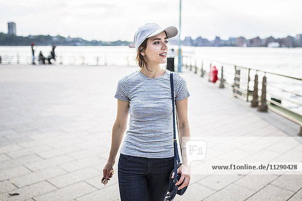 Frau mit Basecap und Handtasche mit Blick auf Distanz