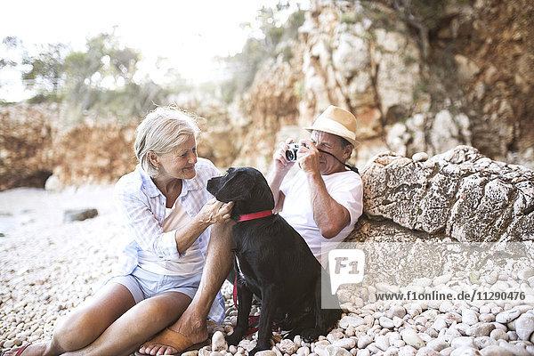 Seniorenpaar entspannt mit Hund am Strand