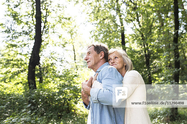 Fröhliches Seniorenpaar beim gemeinsamen Entspannen im Wald