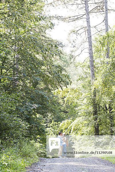 Ein glückliches älteres Paar  das sich im Wald küsst.
