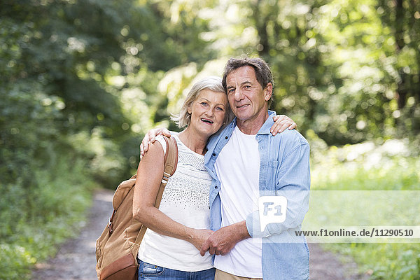 Portrait of happy senior couple relaxing together in the woods