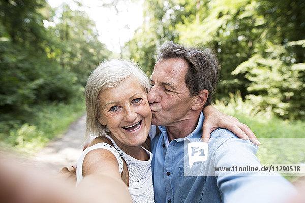 Glückliches älteres Paar  das Selfie in den Wäldern nimmt.